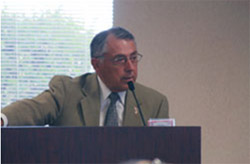 Man speaking from a podium at the first GQCHCC meeting